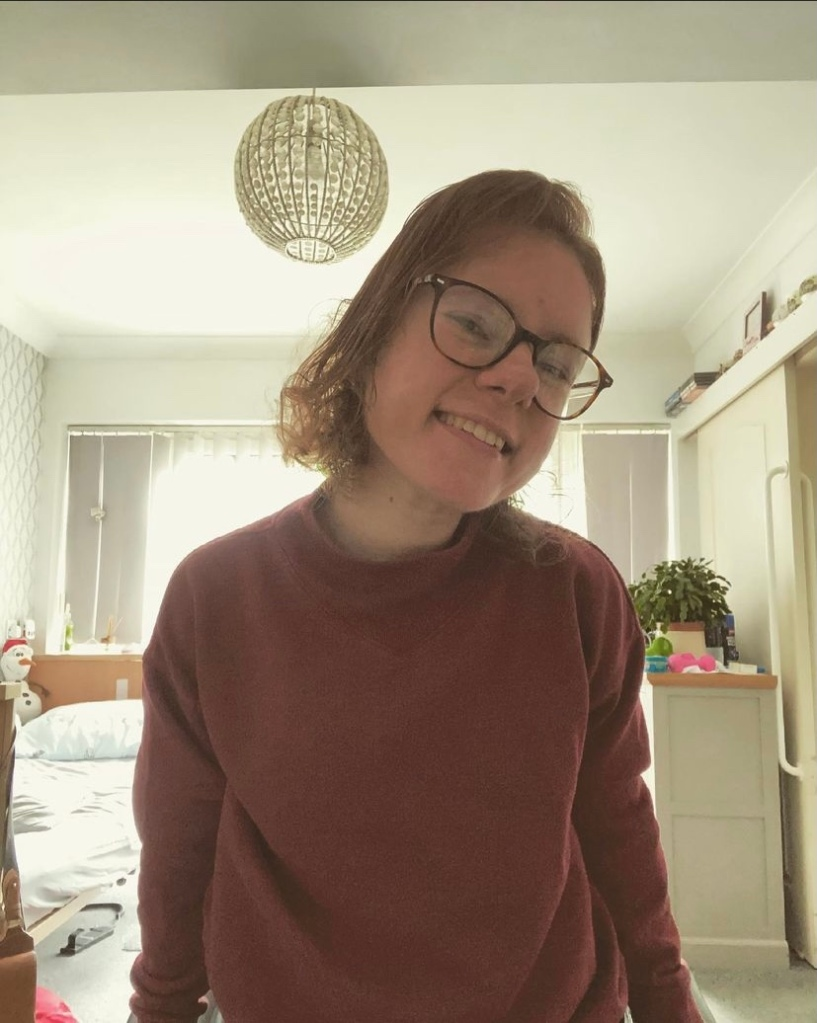 A picture of Danielle standing awkwardly from her wheelchair and smiling. She is wearing a burgundy jumper, has short brown hair and wears glasses. In the background, you can see that her bed is messy. There's also a plant and some weights on the chest of drawers behind her.