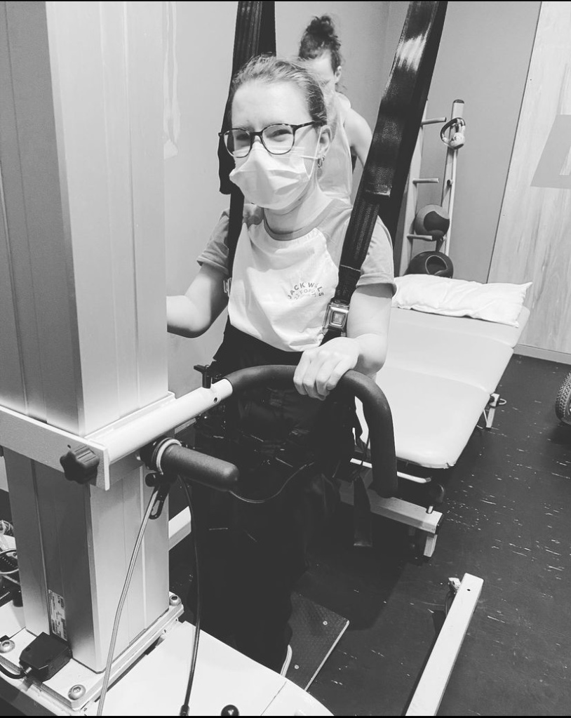 A black and white photo of Danielle using a hoist to stand in physiotherapy. She is wearing a mask but her eyes look happy because she is smiling at the camera. She is holding on for dear life.