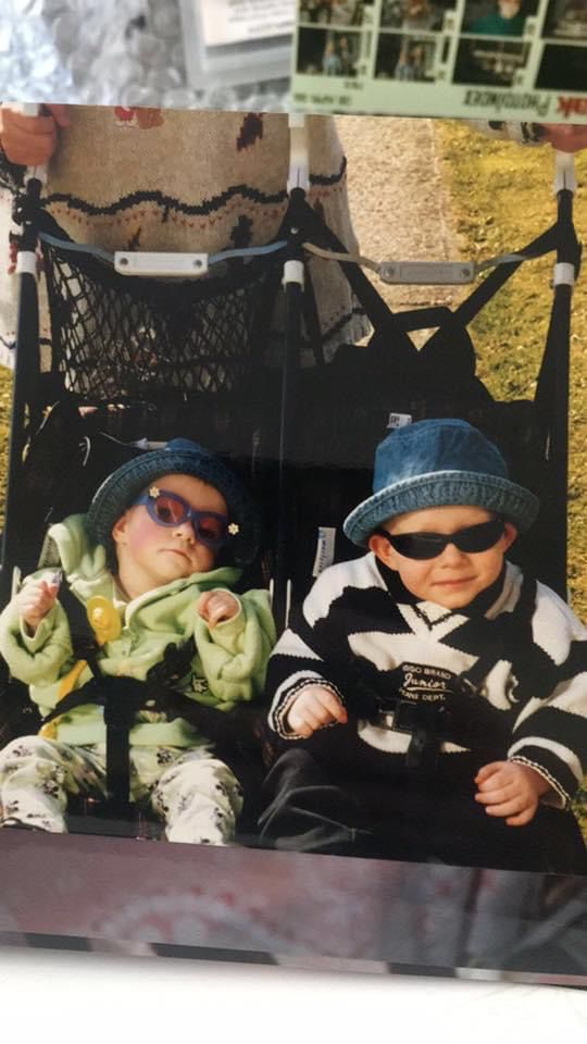 A picture of Danielle with her brother, Jack, from when they were small children. They are in a twin buggy, both wearing sunglasses and blue hats. Danielle is wearing a green jumper with white leggings. Jack is wearing a white top with black stripes and black trousers.